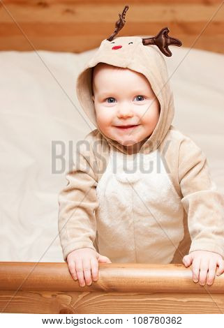 Cute little baby girl wearing christmas deer costume looking at camera smiling