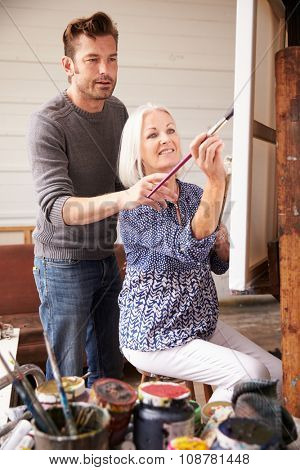 Artist With Female Student In Painting Class