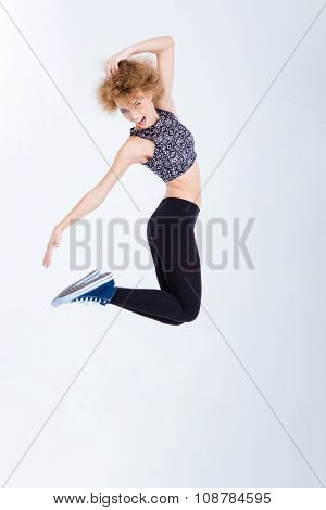 Full length portrait of a young excited woman jumping isolated on a white background