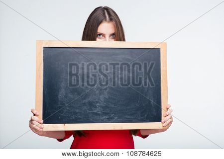 Portrait of a young woman peeping over white board isolated on a white background