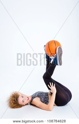 Portrait of a sexy young woman lying on the floor with basketball ball isolated on a white background