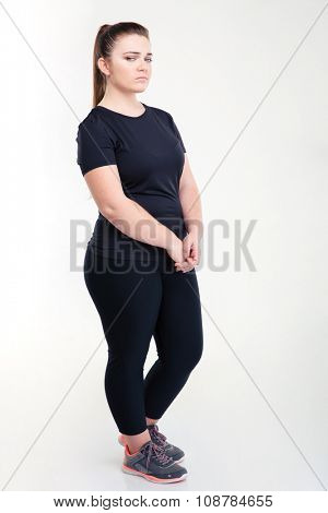 Portrait of a fat sad woman in sportswear standing isolated on a white background