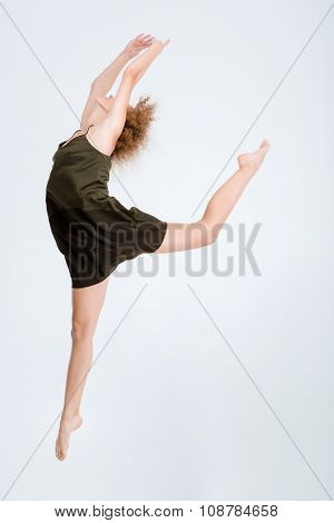 Full length portrait of a young woman dancing isolated on a white background