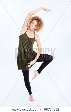 Full length portrait of a young female ballerina posing isolated on a white background