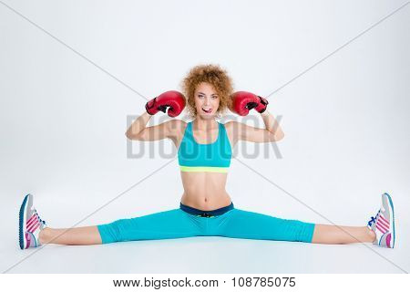 Portrait of a fitness woman in boxing gloves doing twine and showing her biceps isolated on a white backgorund