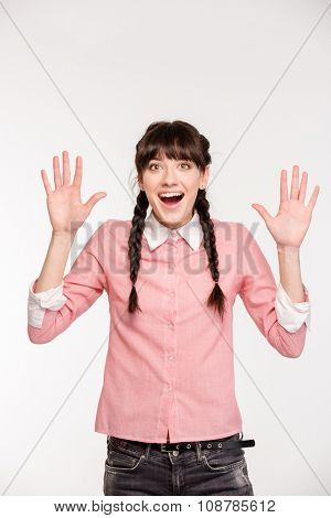 Portrait of amazed young woman standing with raised hands up isolated on a hwite background