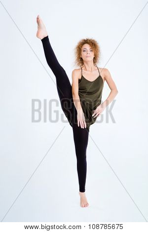 Full length portrait of a flexible woman with curly hair posing isolated on a white background