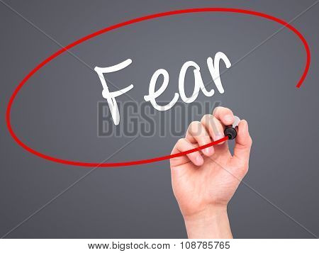 Man Hand writing Fear with black marker on visual screen.