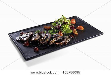 Fried slices of veal with salad mix on white background