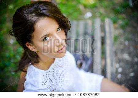 Woman On A Bench Looking At Camera From High Angle