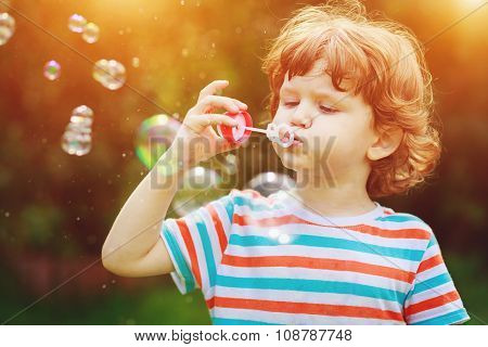 Child Blowing Soap Bubbles In Summer Park.