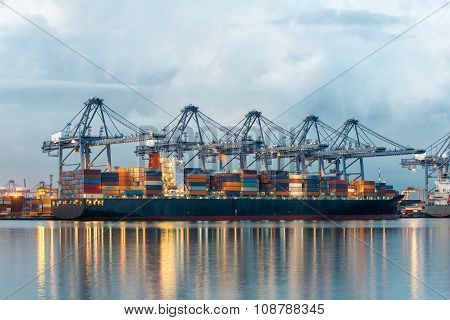 Container Cargo Freight Ship With Working Crane Bridge In Shipyard For Logistic Import Export Backgr