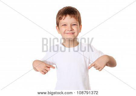 Happy Little Boy Pointing His Fingers On A Blank T-shirt, A Place For Your Advertising.