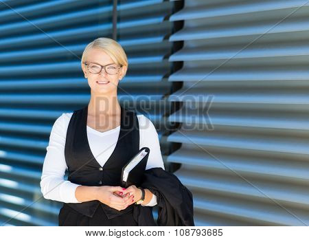 Beautiful businesswoman with a diary outdoor.