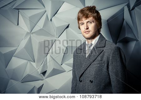 Portrait of a handsome man in an elegant coat. Beauty, fashion. Studio shot.
