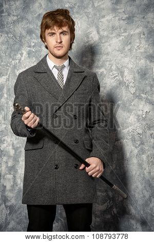 Handsome young man in an elegant coat. Beauty, fashion. Studio shot.