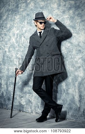 Full length portrait of a handsome young man in an elegant hat and a coat. Beauty, fashion. Studio shot.