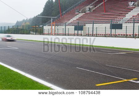 motosports, weather, extreme and race concept - close up of car driving on speedway track or road and stands under rain