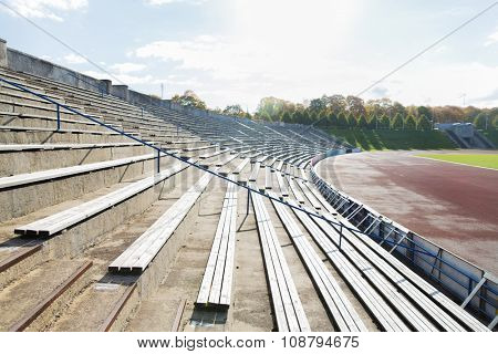 sport and architecture concept - stands with rows with benches on stadium