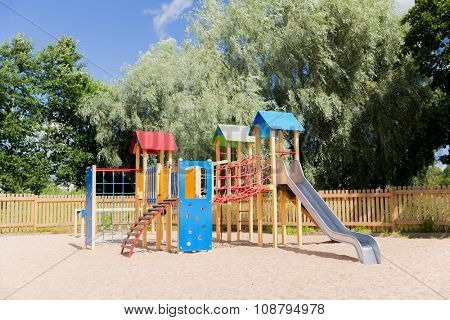 childhood, equipment and object concept - climbing frame with slide on playground outdoors at summer