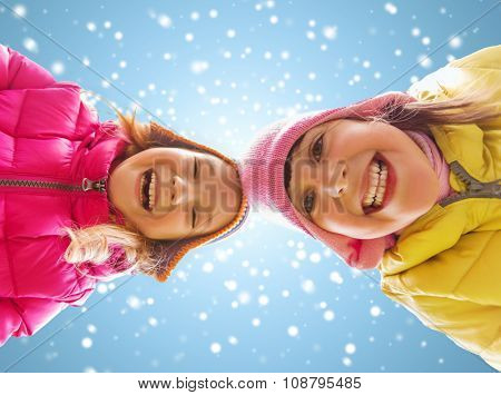 childhood, friendship, christmas, winter and people concept - happy little girls faces outdoors over blue sky and snow background