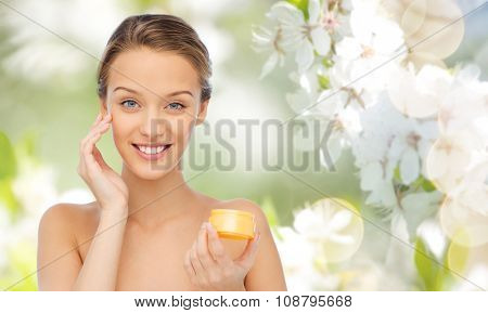 beauty, people, cosmetics, skincare and cosmetics concept - happy young woman applying cream to her face over summer green natural background with cherry blossom