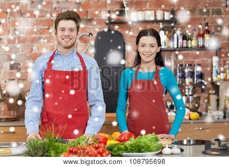 cooking class, culinary, food and people concept - happy couple in kitchen over snow effect