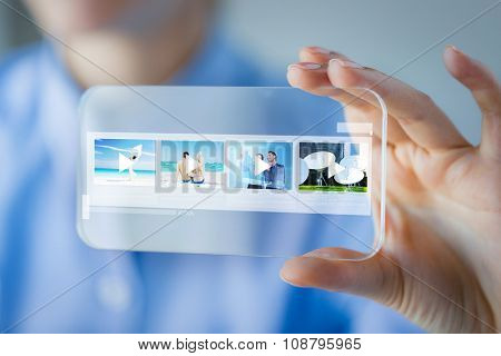 business, technology and people concept - close up of woman hand holding and showing transparent smartphone with media player icons on screen at office