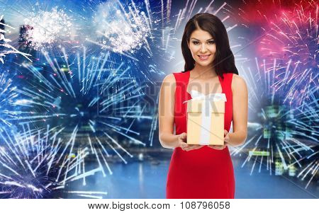 people, holidays, christmas, new year party and celebration concept - beautiful sexy woman in red dress with gift box over night city and firework background