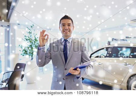 auto business, car sale, consumerism, gesture and people concept - happy man with clipboard showing thumbs up at auto show or salon over snow effect
