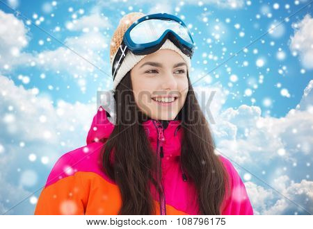 winter, leisure, sport and people concept - happy young woman in ski goggles over blue sky and clouds background