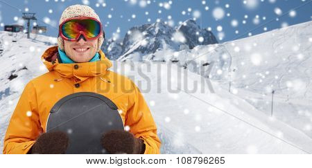 winter, leisure, sport and people concept - happy young man in ski goggles over snow and mountain background