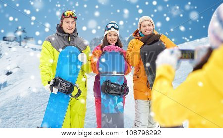 winter sport, technology, leisure, friendship and people concept - happy friends with snowboards and smartphone taking picture over snow and mountain background