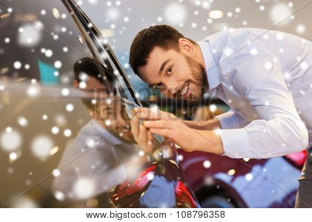 auto business, car sale, consumerism and people concept - happy man touching car in auto show or salon over snow effect