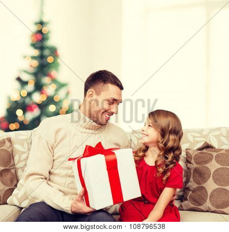 family, christmas, x-mas, winter, happiness and people concept - smiling father and daughter holding gift box and looking at each other
