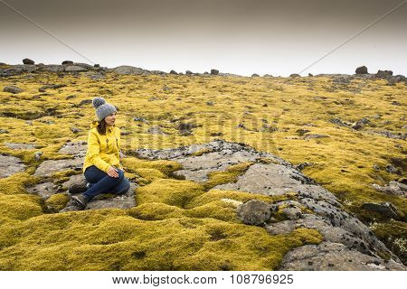 Beautiful young woman sitting on a rock and surrounded by Icelandic moss