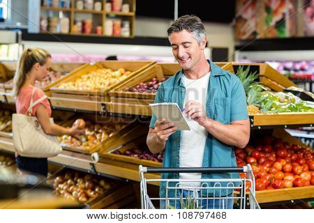 Smiling man looking at the grocery list at the supermarket