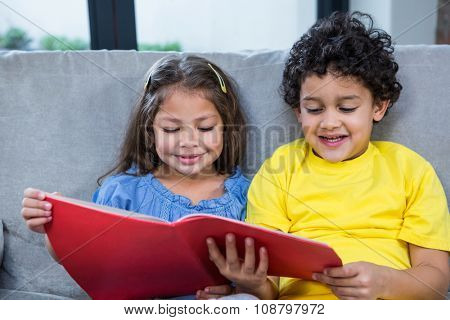 Cute siblings reading a book on the sofa in living room