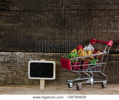 Shopping cart full of colorful gift boxes and blank sign over wooden background
