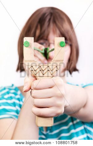Front View Of Girl Shooting From Wooden Slingshot