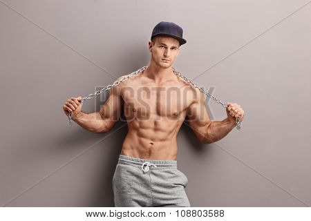 Shirtless male gangster holding a metal chain and leaning against a gray wall