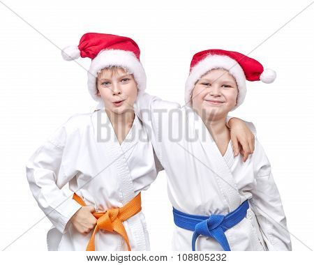 Cheerful friends hugging in a kimono and wearing Santa hat
