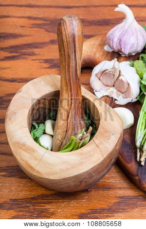 Wood Mortar With Cilantro Herb And Garlic On Table