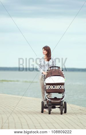 Young Mother With A Stroller
