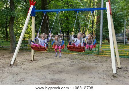 Four Clones Of Cute Little Girl Swinging On Swing