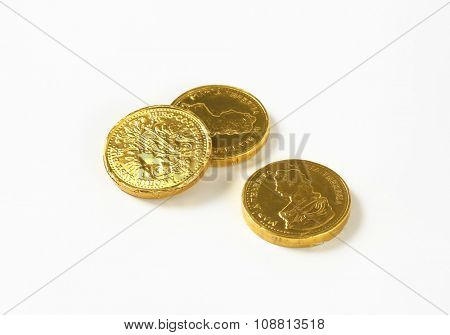 three chocolate coins on white background