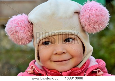 Portrait Of A Smiling Baby Girl In A Pink Hat