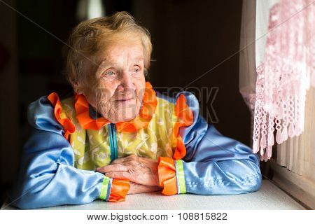 Old woman in Slavic ethnic costume sits at a table near the window.
