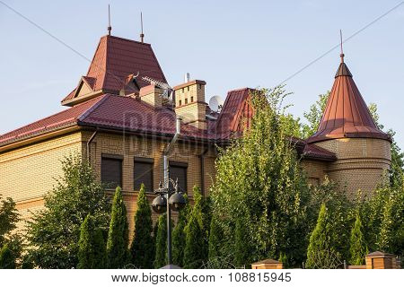 Kiev, Ukraine - July 15, 2015: Orange Modern Country House With Red Roof, Garden Of Trees On Backgro