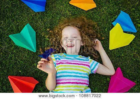 Happy Laughing Girl Throwing Paper Airplane In Green Grass At Summer Park. Happy Childhood, Travel,